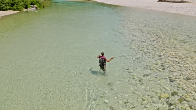 AERIAL Fisherman fly-fishing on the mountain river with a beautiful view