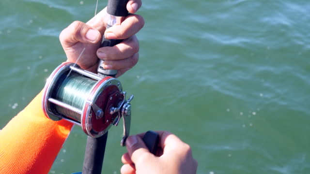 fisherman holding rod with ocean background - fishing rod stock videos & royalty-free footage