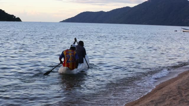 fisherman in a traditional dug out canoe at cape maclear on lake malawi malawi africa - oar stock videos & royalty-free footage