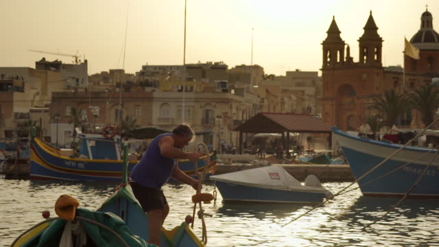 fisherman in boat at sunset - malta - malta stock videos & royalty-free footage