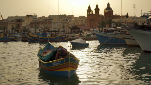 fisherman in boat at sunset - malta - catholicism stock videos & royalty-free footage