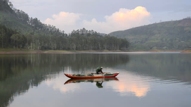 Fisherman in his fishing boat at Maussakele Reservoir in the Nuwara Eliya District of the Sri Lanka Highlands, Sri Lanka, Asia