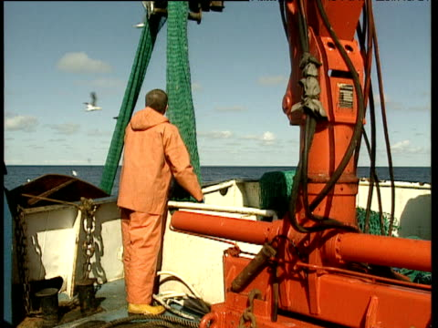 vídeos de stock e filmes b-roll de fisherman in orange overalls pulling fishing net onto trawler as seagulls swarm overhead - rede de pesca comercial
