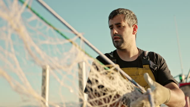 fisherman in protective workwear hauling in net - fisherman stock videos & royalty-free footage