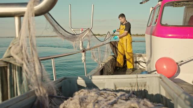 fisherman lowering trawl net into water - fisherman stock videos & royalty-free footage