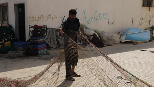 fisherman mends a fishing net on may 11, 2018 in gaza city, gaza. for the 1.9 million palestinians living inside the gaza strip life has become a... - 14 15 years stock videos & royalty-free footage