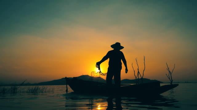 vidéos et rushes de pêcheur sur la pêche de bateau de longtail au coucher du soleil en thaïlande - lancer la ligne de canne à pêche