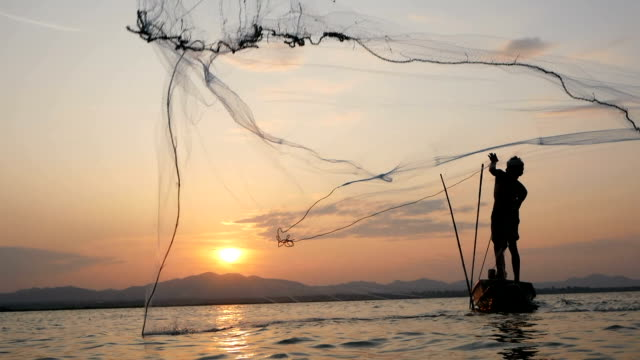fisherman on longtail boat fishing - fishing net stock videos & royalty-free footage