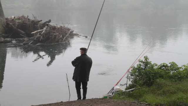 Fisherman on river side in autumn