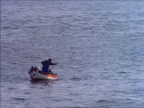 fisherman on small boat pulling in net / portugal - cinematography stock videos & royalty-free footage