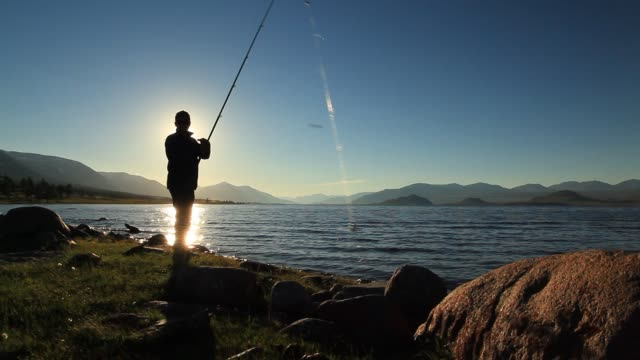 fisherman on the lake at sunset - fishing rod stock videos & royalty-free footage