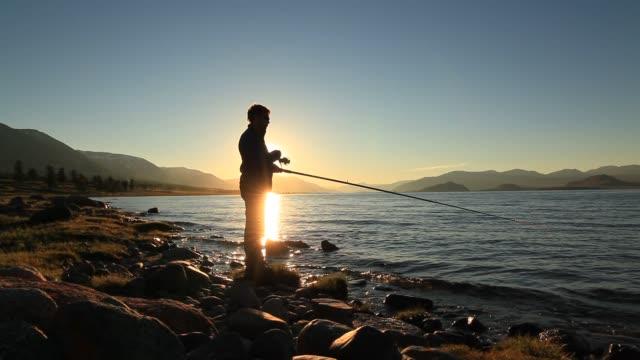 Fisherman on the lake at sunset