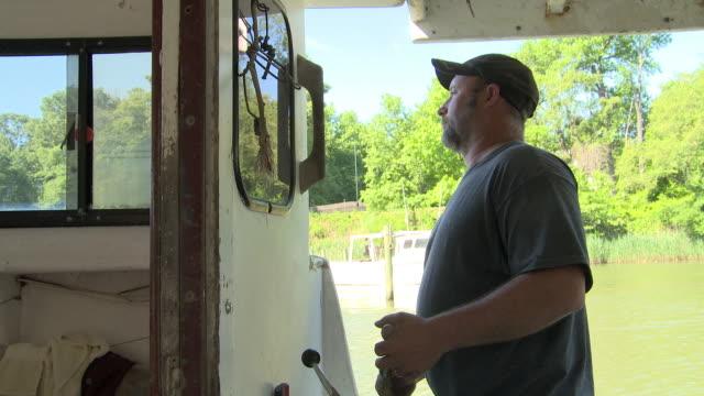 stockvideo's en b-roll-footage met fisherman pilots his boat on the chesapeake bay - visser