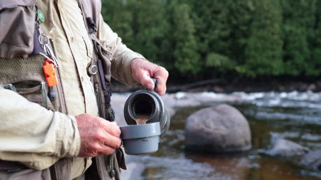 fisherman pouring a coffee cup in nature - fishing reel stock videos and b-roll footage