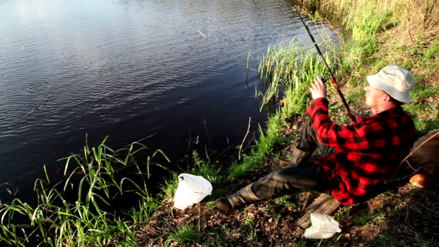 fisherman pulling a fish from the water - fisherman stock videos and b-roll footage