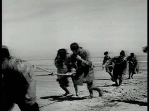 Fisherman pulling long rope in desert Fishermen standing in seawater gathering in large fish net teamwork CU Fish caught in net