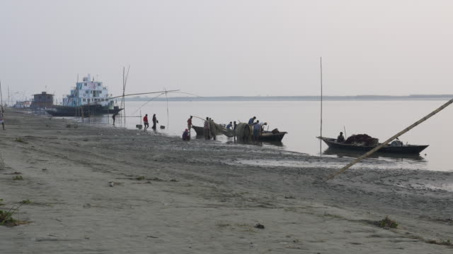 fisherman return to the banks of the river jamuna bangladesh at sunset to unload sell auction and share their catch of small fish before tending to nets and returning home - dhaka stock videos & royalty-free footage