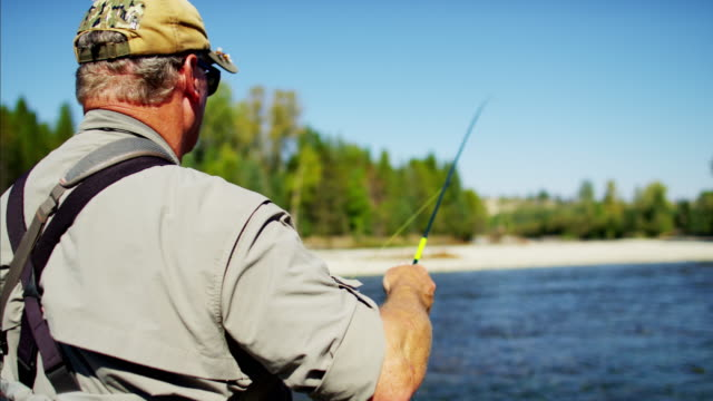 Fisherman rod and reel casting in freshwater river