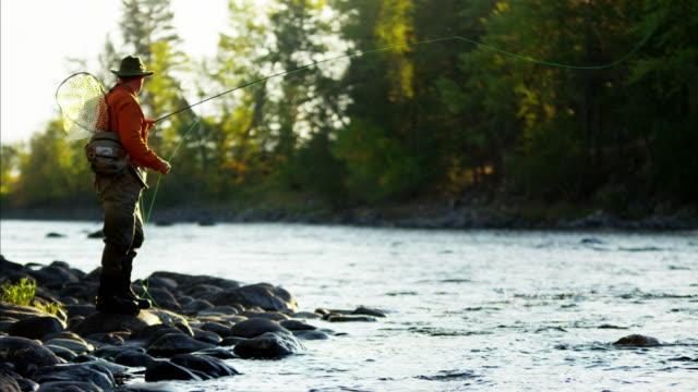 fisherman rod and reel casting in freshwater river - 獲った魚点の映像素材/bロール