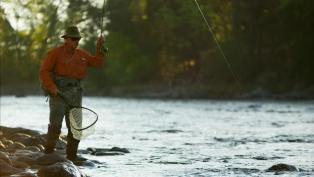 stockvideo's en b-roll-footage met fisherman rod and reel casting in freshwater river - hengel uitwerpen