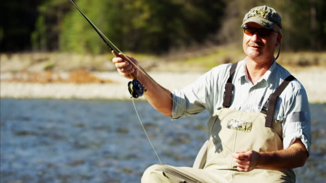 Fisherman rod and reel casting in river USA