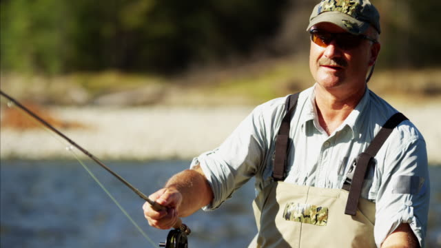 Fisherman rod and reel fishing in river USA