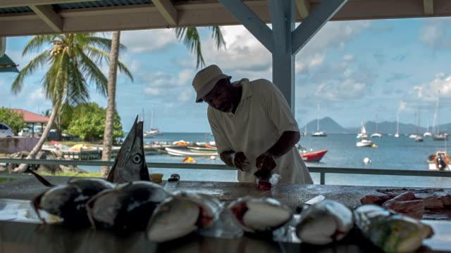 vidéos et rushes de a fisherman sells fish at the fish market of st. anne, martinique - martinique