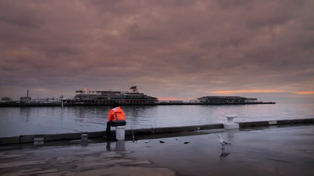 ms fisherman setting on princess pier with station pier seen behind at dusk / melbourne, victoria, australia - fishing industry stock videos & royalty-free footage