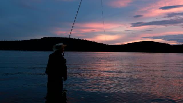 vídeos y material grabado en eventos de stock de pescador silueta al atardecer - caña de pescar