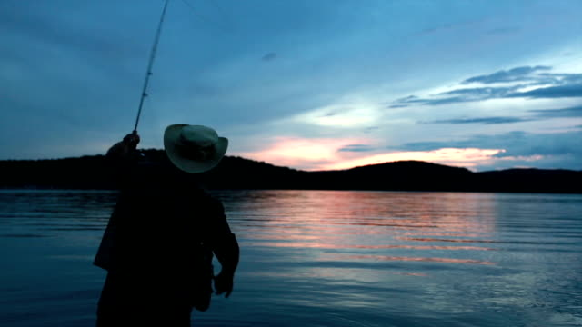 fisherman silhouette at sunset - pole stock videos and b-roll footage