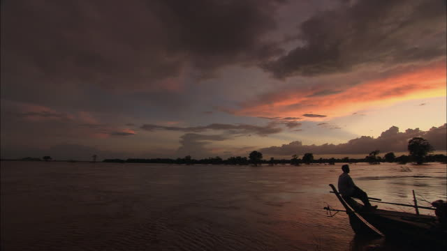 ws pan fisherman sitting in boat under sunset sky, cambodia - cambodia stock videos and b-roll footage