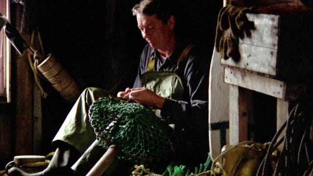 Fisherman sitting in boathouse mending fishing net / Nova Scotia, Canada