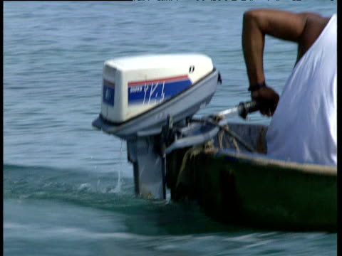 fisherman steers outboard motor of small fishing boat at sea trinidad and tobago - menschliche gliedmaßen stock-videos und b-roll-filmmaterial