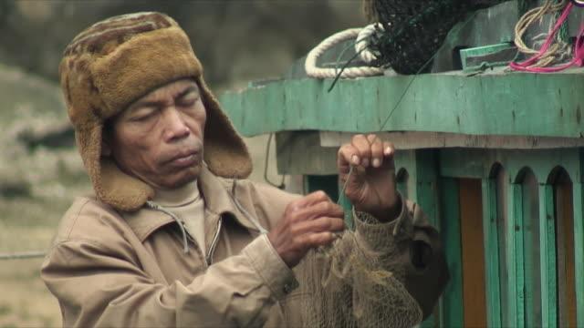vídeos y material grabado en eventos de stock de cu zo ms fisherman trying to undo knot with teeth, halong bay, vietnam - lazo nudo