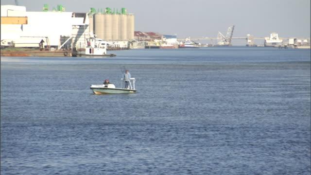 vidéos et rushes de a fisherman turns his boat in a river near a factory in new orleans. - chapeau de paille