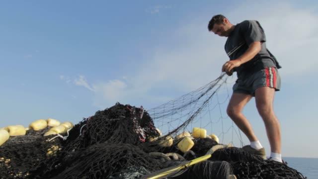 fisherman working on the net - 男漁師点の映像素材/bロール