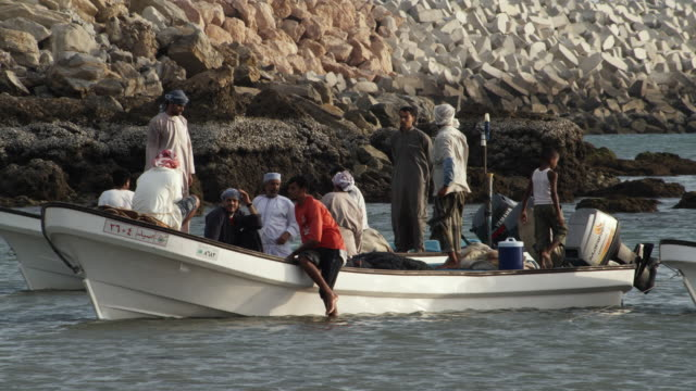 MS Fishermen and children examining catch in fishing boat / Sur, Oman