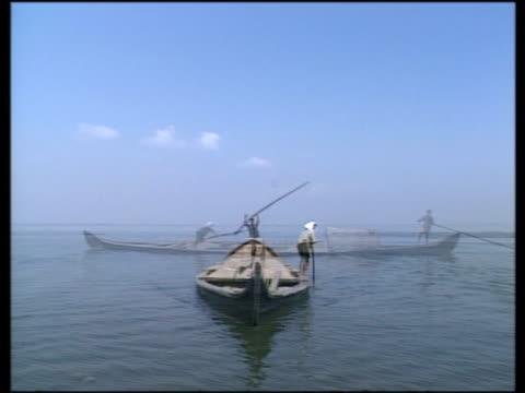 vídeos de stock, filmes e b-roll de fishermen and their boats at work in coastal kerala - indústria da pesca