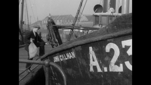 montage fishermen arrive at the docks and board a trawler / aberdeen, scotland, united kingdom - aberdeen schottland stock-videos und b-roll-filmmaterial