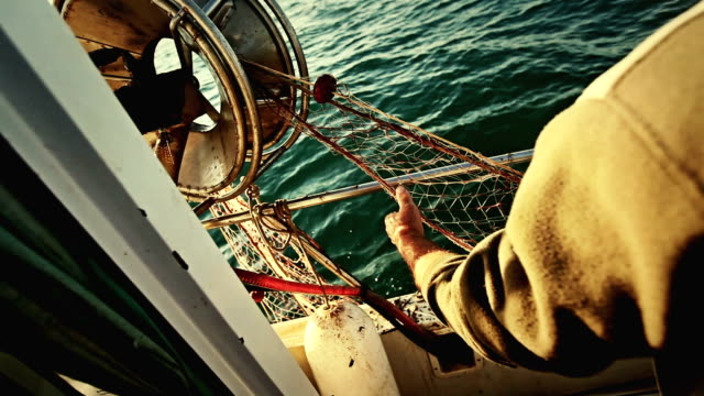 Fishermen at work, cleaning the nets on fishing boat