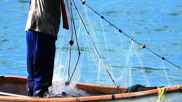 職場では、漁師が漁船の網を集める - 水産業点の映像素材/bロール