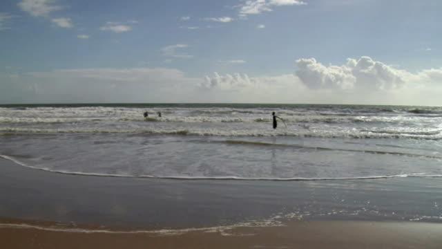 ws fishermen dragging fishing net through sea / trinidad and tobago - kelly mason videos stock videos & royalty-free footage