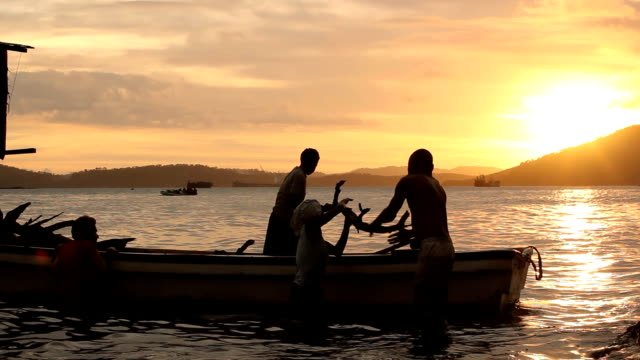 Fishermen emptying their boat at sunse Papua New Guinea is an island located in Oceania There are around 850 languages spoken on the island and there...