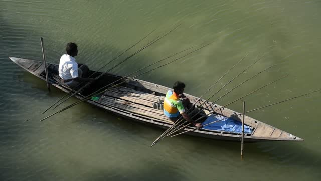 fishermen fishing with ten fishing rods sitting on a boat in a lake at a village in barpeta, india on december 03, 2020. fisheries in india is a very... - fishing industry stock videos & royalty-free footage