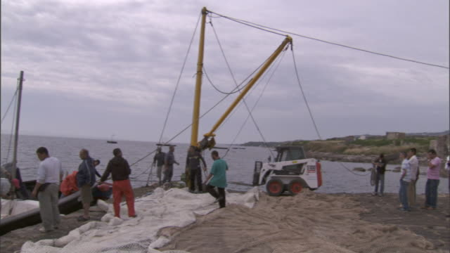 fishermen gather on the beach where a large net has been spread. - hoisting stock videos & royalty-free footage