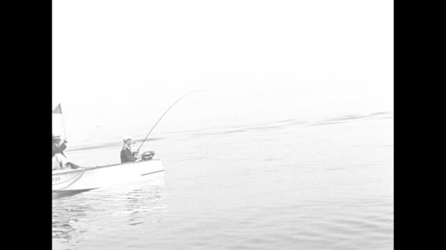 fishermen getting into their boats and launching boats, large crowd on shore watching / fishermen moving along in their boats / fisherman catching... - スポーツの判定員点の映像素材/bロール