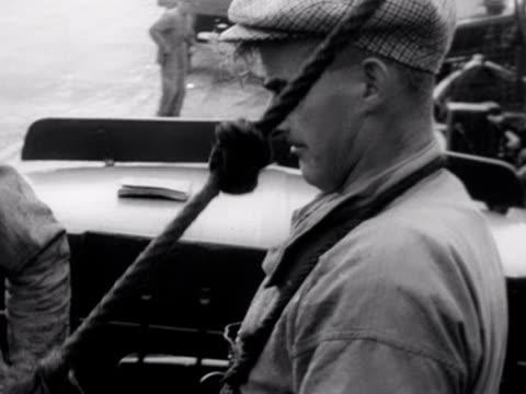 vídeos de stock, filmes e b-roll de fishermen haul baskets of herring from their boat to the quayside at stornoway - indústria da pesca