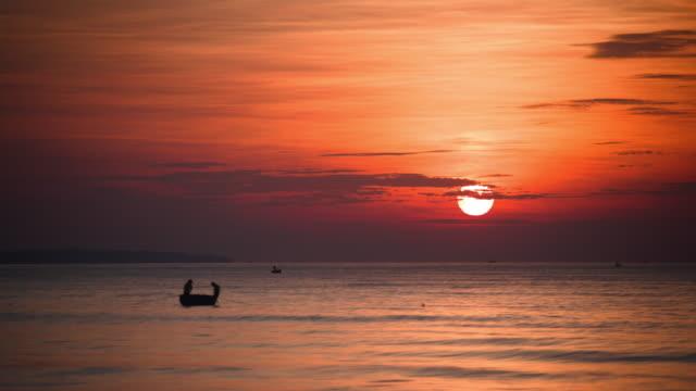 vídeos de stock e filmes b-roll de fishermen in a tiny boat as the brilliant morning sun rises - embarcação de lazer