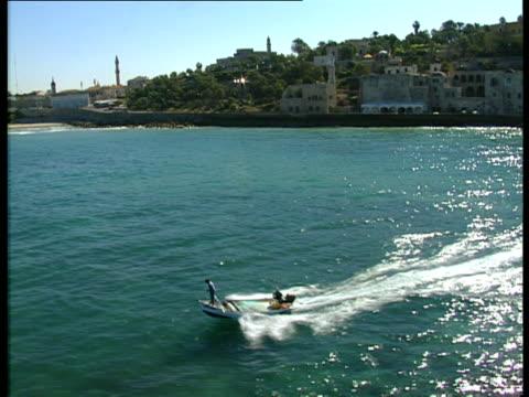 aerial ws fishermen in boat near old city of jaffa with skyline of tel aviv, dan metropolis, israel - jaffa stock videos & royalty-free footage