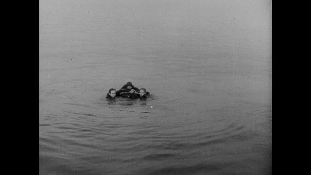 b/w fishermen in dory approaching shot-down airmen floating and gripping wreckage, hauling them aboard, and helping them dump water from their boots / rosyth, scotland, united kingdom - fluss firth of forth stock-videos und b-roll-filmmaterial
